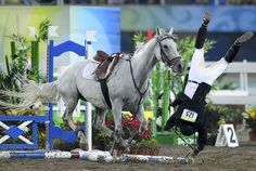 Cao Zhongrong of China falls from his horse ChuChu during the men's riding show jumping event in the modern pentathlon competition. He ranked 30th after the event.