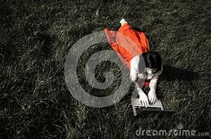 A young woman interacting with a laptop whilst lying down on grass. Soft focus, desaturation, glow and overexposure used for effect.