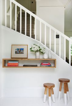 A floating shelf and paint-dipped stools functions as an elegant drop zone in the relatively petite entry.