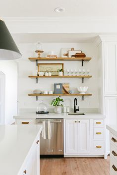 White kitchen cabinets, brass pulls, floating wood shelves, industrial black light fixtures | House of Jade Interiors