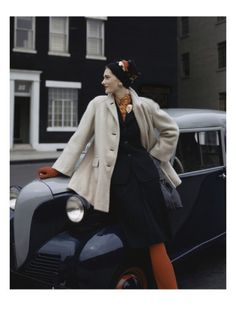 Vogue - August 1942. An exquisite automobile parked on a street presents an extremely chic setting for a fashion photograph. A model wears a wool gabardine suit topped with a camel-hair nylon fleece coat. Her burnt-orange hosiery and gloves add warmth to this coolly stylish scene. John Rawlings's work appeared in the August 16, 1946, Vogue.