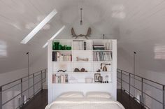 The bookshelf holds a curated collection of objects and reading material. The iron railings on either side of the platform are covered with ...
