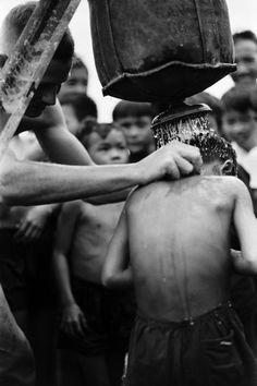 Um médico dá a um grupo de crianças vietnamitas um chuveiro com um saco de Lyster. Nomes, data e local desconhecidos.