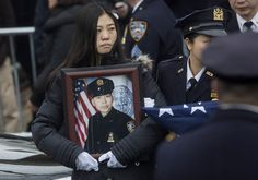 Pei Xia Chen, the widow of New York City Police Officer Wenjian Liu, holds his picture following his funeral service at Aievoli Funeral Home in the Dyker Heights neighborhood on January 4, 2015 in the Brooklyn.
