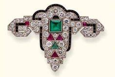 JANESICH, Belle broche art déco, au centre une émeraude taille émeraude, entouré de diamants taille brillant, rubis et émeraude triangles sur platine, 5cm7 de large, 1925