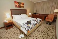 Guests are invited to relax and enjoy the bustling city of Luanda in Angola from the comfort of the four-star Skyna Hotel Luanda. Hotels, Relax, African, Bed, Furniture, Home Decor, Decoration Home, Stream Bed, Room Decor