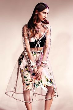 Clear vinyl trench coat with pale pink trim and stud embellishments worn with floral print skirt and cropped top.. DIY the look yourself: http://mjtrends.com/pins.php?name=clear-vinyl-material-for-coat_1
