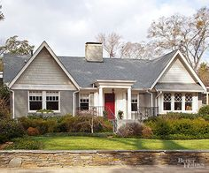A neutral palette is perfect for this eclectic-style house because of the details, such as divided-light windows, a columned portico, and lots of texture. The brick walls are painted a slightly darker shade of gray than the shingled gables, offering subtle contrast. The welcoming red door provides a punch of color.