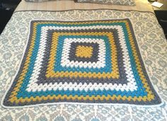 Teal, yellow, gray, and white crochet granny square baby blanket