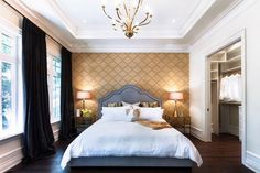 A fancy chandelier charms the white glossy tray ceiling just as the cream-colored patterned wallpaper accents the central wall behind the gray bed. Photo by HUSH