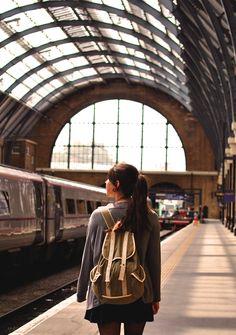 mujer con una mochila en los hombros parada en una estación de tren