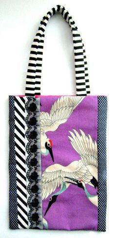 ※こちらの商品は完売いたしました。ピンクがかった紫に、どこか可愛らしい表情の白鶴が優雅に羽ばたくアンティーク着物生地を使用したバッグ。裏面は紺の水玉と、淡い紫色×白の水玉模様の2層作りです。裏地はピンク色サイズ 縦:約26.5センチ、横:約20センチ、持ち手:約16センチ