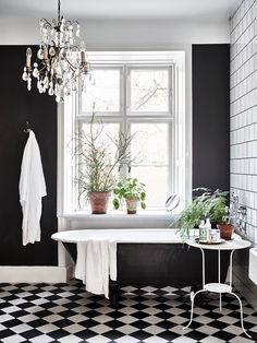 biało-czarna łazienka | biało-czarna szachownica na podłodze + czarna wanna wolnostojąca + kryształowy żyrandol + rośliny doniczkowe
