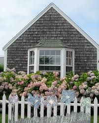 shaker siding, white picket fence and cottage roses.... looks like Nantucket