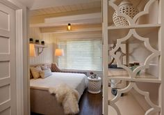 Cottage guest room features planked ceiling accented with box beams and a glass bell jar pendant ...
