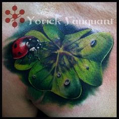 Realistic lady bug and four leaf clover tattoo in full color.