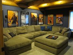 Home theater room, with a big couch and popcorn machine and movie posters on the walls bug shelf for the DVD