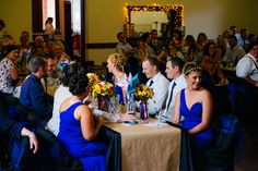Bright Royal Blue and Yellow themed vintage wedding. Long sleeved lace wedding dress. Long royal blue bridesmaid dresses. Bright flower bouquets. Wedding dog wore a yellow and blue bow tie. Calvin Klein shirt. Marc Jacobs ties. Winery photo shoot. Photos also done in the Maxwell Winery maze. Photography by Jay Wennington. DIY decorations, including paper pinwheels, kraft paper table runner and rosette backdrop. Budget wedding. Hopefully our wedding will give other people some wedding ideas!