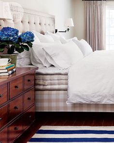 Master bedroom In the master bedroom, the cozy linen headboard, stunning sconces and luxurious Hästens bed, with its signature plaid pattern...