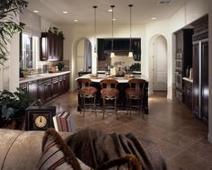 Wide open design for this kitchen includes expanse of dark marble flooring reaching living room area, with ornate seating at large black island with white marble countertop. Dark wood cabinetry all around adds contrast to white walls and arch doorways.