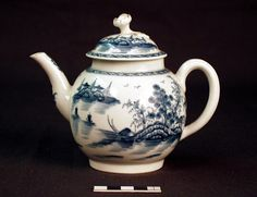 Worcester porcelain teapot and cover; globular with S-shaped spout, ribbed coop handle and low domed cover with open flower knob with stem and two leaves; painted in underglaze blue with a Chinese river scene  Materials: porcelain  Measurements: 124 (height) 160 (width)  Accession number: NWHCM : 1946.70.472