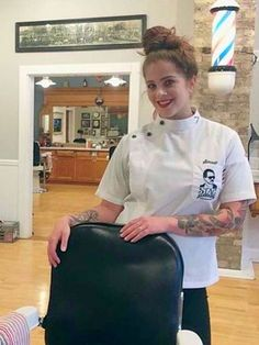 You walk into the shop and see a pretty young lady with her hair in a bun and wearing a tightly buttoned barber jacket. She has a white pinstripe cape slung over her left arm and she is stropping a...