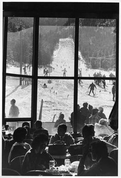 Colorado Springs  Ski Broadmoor (1964) View from inside Winter House at Ski Broadmoor up the slope with skiers. People inside the building are ea