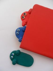 Fimo bookmark monster - I'd alter this to include a fabric bookmark with feet attached at the bottom.  Yep.