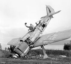 A GI is seen waving from the cockpit of a downed German Focke-Wulf Fw 190 fighter aircraft, Pocking, Bavaria, Germany, World War II, July 1945