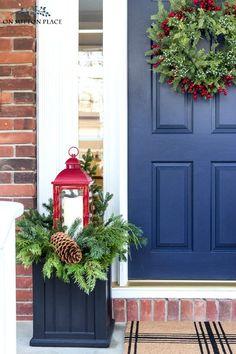 Ideas for easy Christmas porch decor. Winter planter idea using red lanterns. Festive Christmas wreath along with a cozy Christmas sitting area.