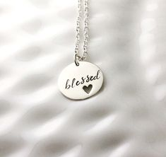 I love this little blessed necklace! The sterling silver 5/8 disc has a small heart cutout and is hand stamped with the word blessed in one of my