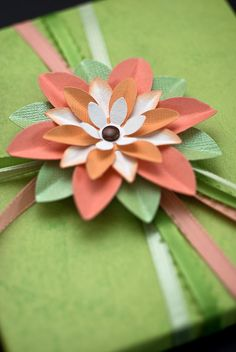 The flower is composed of five layers of scrapbooking paper petals held together by a brad in the center~