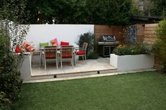 Classic BBQ and eating area - white walls, decking, paving, built-in seating