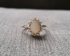 This Stunning Antique Ring features a 14K Antique Gold Setting with 1 carat Natural Opal and 12 Natural Diamonds measuring .12 carats. Makes a great Gemstone Engagement Ring Alternative or right hand ring.    Size 4.25