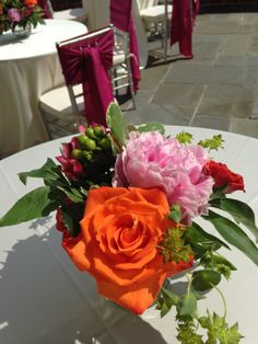 WEDDING LOW CENTERPIECE: This bride's color palette was pink and orange. We accommodated her with orange roses, pink peonies, gorgeous pink gerber daisies and orange gerber daisies, orange calla lilies, stargazer lilies, orange alstroemerias and pink alstroemerias, with accents of white and green of white hydrangea and green hypericum berries. This was a low centerpiece for the wedding reception tables. www.WilliamsburgFloral.com www.facebook.com/WilliamsburgFloral