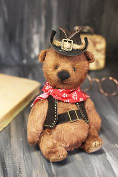 """The teddy bear and it's outfit are hand-made. The body is made out of brown fur. His cowboy outfit consists of a hat, vest, and belt made of dark brown leather.  To top of the look, the teddy is wearing a stylish red and white shawl.  All clothes are fully removable. The bear has black eyes and the nose is made out of fleece.   height approx. 13 cm / 5.1 """" from head to toes (approx. 11 cm / 4.3"""" sitting) tall and is filled with sawdust and granulated quartz for added weight and stabili Panda Bear, Polar Bear, White Shawl, Cowboy Outfits, Hyena, Lemur, Orangutan, Chipmunks, Dark Brown Leather"""