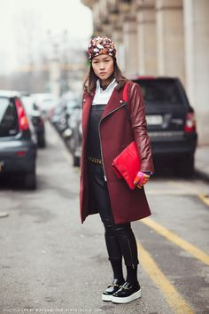 Stefanie in a print turban, ZARA burgundy coat, black pleather overalls, red iPad case, and knit gloves.