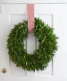 In this fresh, fragrant door display, a lone loop of scarlet-striped fabric showcases the natural beauty of a bushy bay leaf wreath.  - GoodHousekeeping.com
