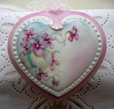 This sweet powder box is heart-shaped with a lovely sprig of violets. It is hand-painted and signed. The bottom and top edges are painted a soft rose. The top edge has a round beaded detail in the porcelain, as does the bottom piece edge.