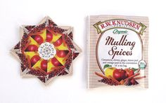 The rosette on the left is made from folding 8 squares of wrappers made from the mulling tea bag wrappers like the one on the right.