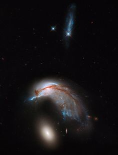 Arp 142, a pair of galaxies that resemble a penguin and an egg, in a new image from the Hubble Telescope.