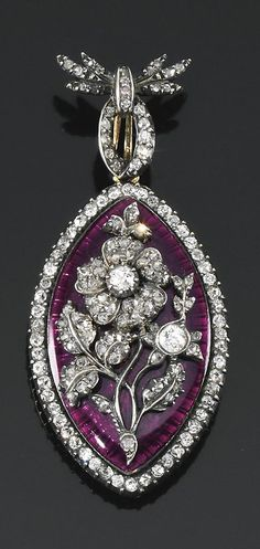 """Enamel and diamond pendant, circa 1899. the navette shaped pendant applied with a central diamond set motif within radiating surrounds enhanced with purple enamel, to a frame and suspension loop accented with circular-cut diamonds, the reverse with a glazed compartment containing a hair locket, inscribed """"From Victoria 1899"""" fitted case stamped Collingwood & Co, 46 Conduit St, London."""