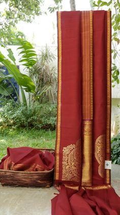 This kanchivaram silk is in garnet red with berry red thread work and gold zari work. the border is in berry red, gold zari and berry blue and crimson red thread work and the pallu is in garnet red…