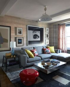 In the den of Tamzin Greenhill's Manhattan apartment, a Minotti sofa has pillows covered in a Le Manach ikat; the pendant light is by Hans Wegner, the stool is by Hervé Van der Straeten, and the rug is by Fort Street Studio. The artwork includes a large Anne Collier photograph, a Damien Hirst butterfly lithograph, and a print series by Wangechi Mutu.   Tour the rest of the home.    - ELLEDecor.com