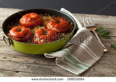 Above with prospective angle shot of pan with baked tomatoes stuffed with rice and chard. by eZeePics Studio, via Shutterstock
