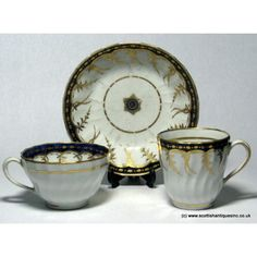 """New Hall Trio c1795 Pattern 248; 1790 to 1797  Pattern 248 Described by Godden as """"Under glaze mazarine-blue band with gold decoration on the glaze. Gold feathery devices hang from the lower side of the border. Pattern 248: small scattered sprigs in gold""""  Teacup, coffee can and saucer, spiral fluted moulding. Some minor wear to the gilding commensurate with age. Three remaining. We also have some trios  with tea bowls and a sucrier, teapot and tea plates, creamer etc."""