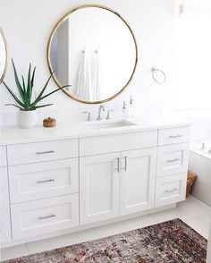 A bright white bathroom with touches of gold and gray.