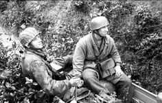 Signalmen from a Fallschirmjäger (Paratrooper) unit check communication lines in France. Of interest is the continued use of the 2nd pattern green step in smock in 1944 despite the wide availability of the Splittertarn camouflaged pattern smock as worn by the Falli on the left.