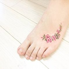 Watercolor style apple blossom tattoo on the left foot.
