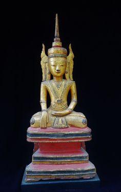 Bouddha paré à l'effigie royale, coiffé d'une importante tiare surmontée d'un haut ushnisha, il est paré de joyaux et est assis en vajrasana sur un haut tertre étagé dans la position de prise de la terre à témoin. Sculpture en bois de teck doré et polychrome. Birmanie. Royaume Shan XVIII eme. Ht:69cm.